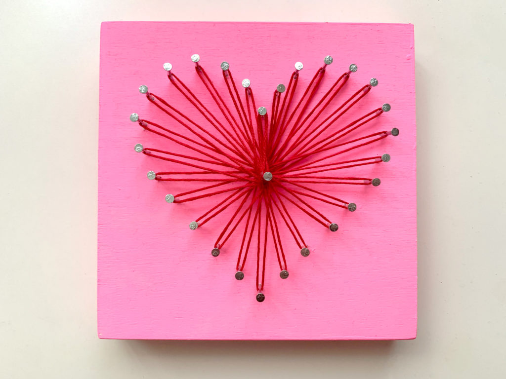 Heart-shaped string art with red thread and a pink wood board