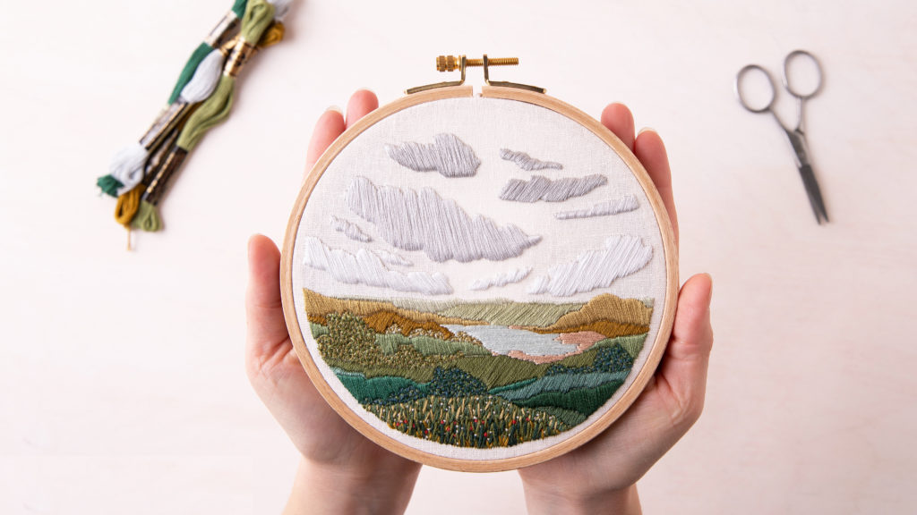 Flat lay on a white table of two hands holding a hand-embroidered landscape of green hills and grey clouds in an embroidery hoop